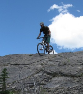 the banshee rune mountain bike riding rock slab on canmore alberta's razors edge trail